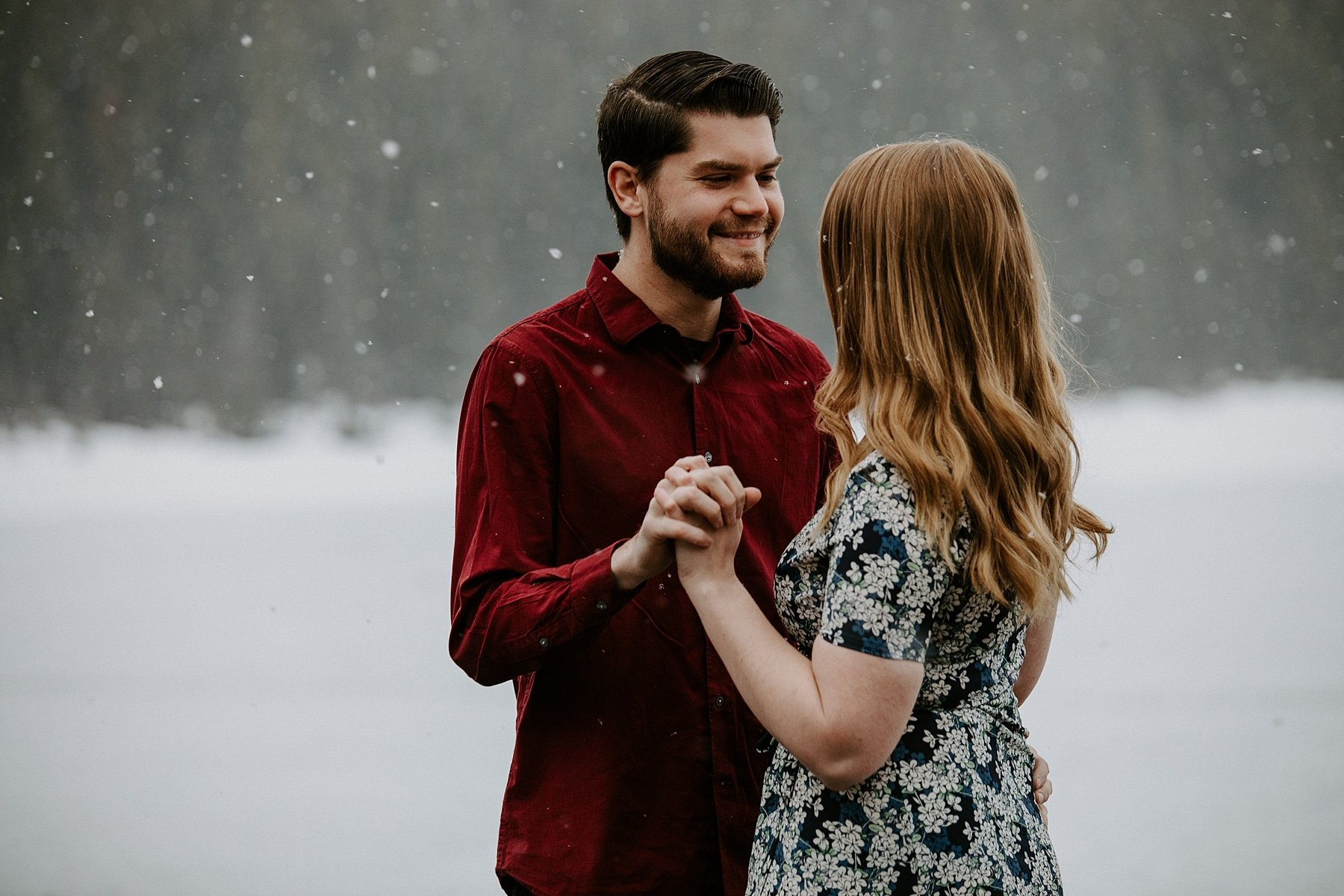 Engaged couple dancing in the snow