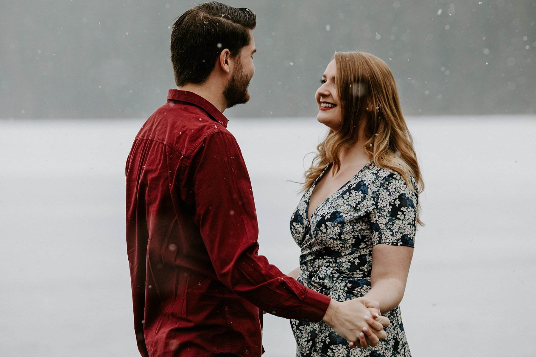 engaged couple dancing in the snow for photos