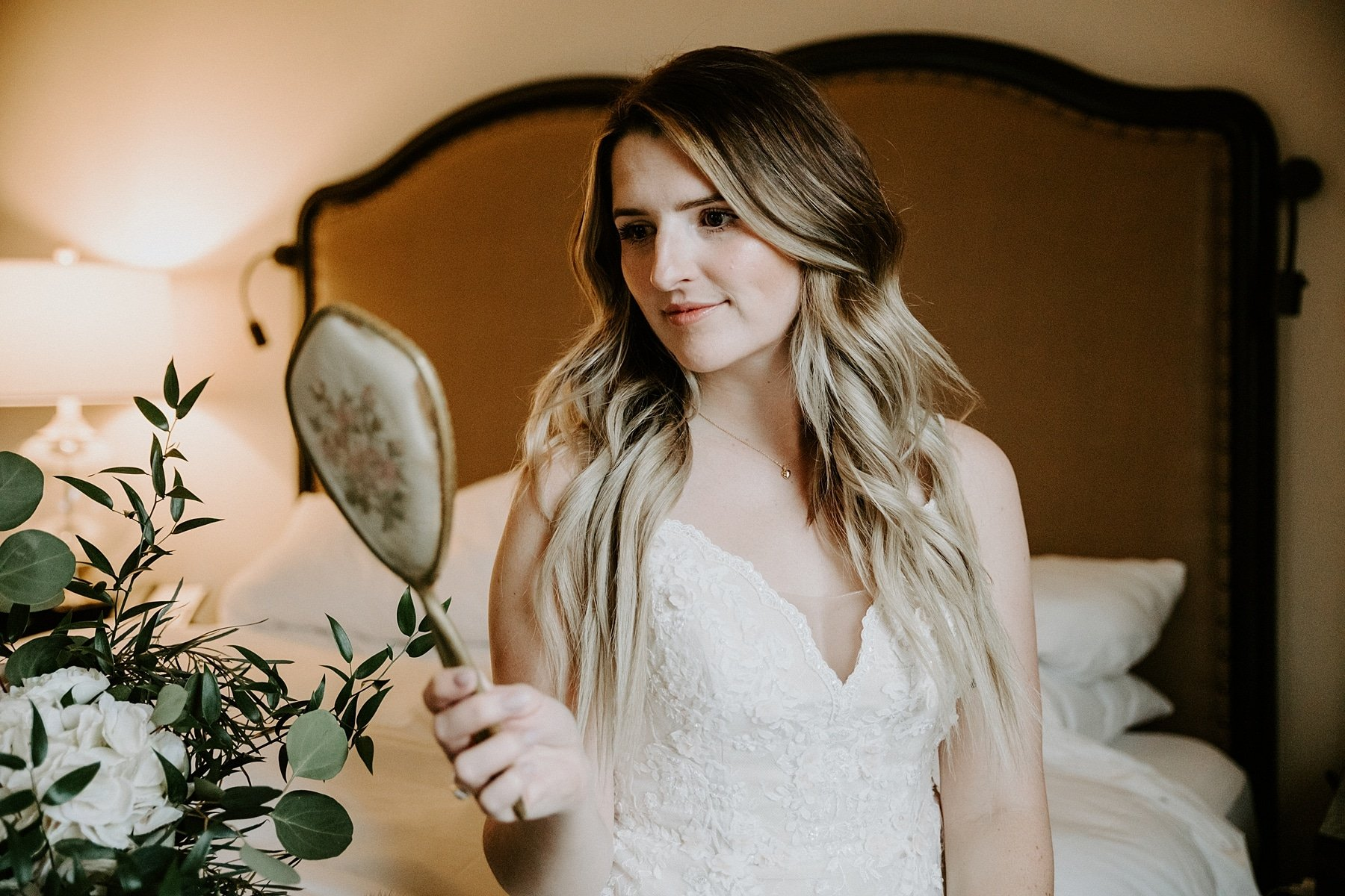 Bride holding vintage mirror up while getting ready for wedding